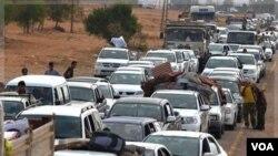 Largas filas de vehículos se alinean para tratar de escapar de Sirte, los cuales son inspeccionados por las fuerzas rebeldes.