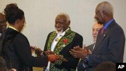 Le sculpteur sénégalais Ousmane Sow, au centre, reçoit son épée académique de Marieme Faye, épouse du président sénégalais Macky Sall, ex-président sénégalais Abdou Diouf, applaudit lors d'une cérémonie à l'Académie française de Paris, le mercredi 11 décembre 2013.
