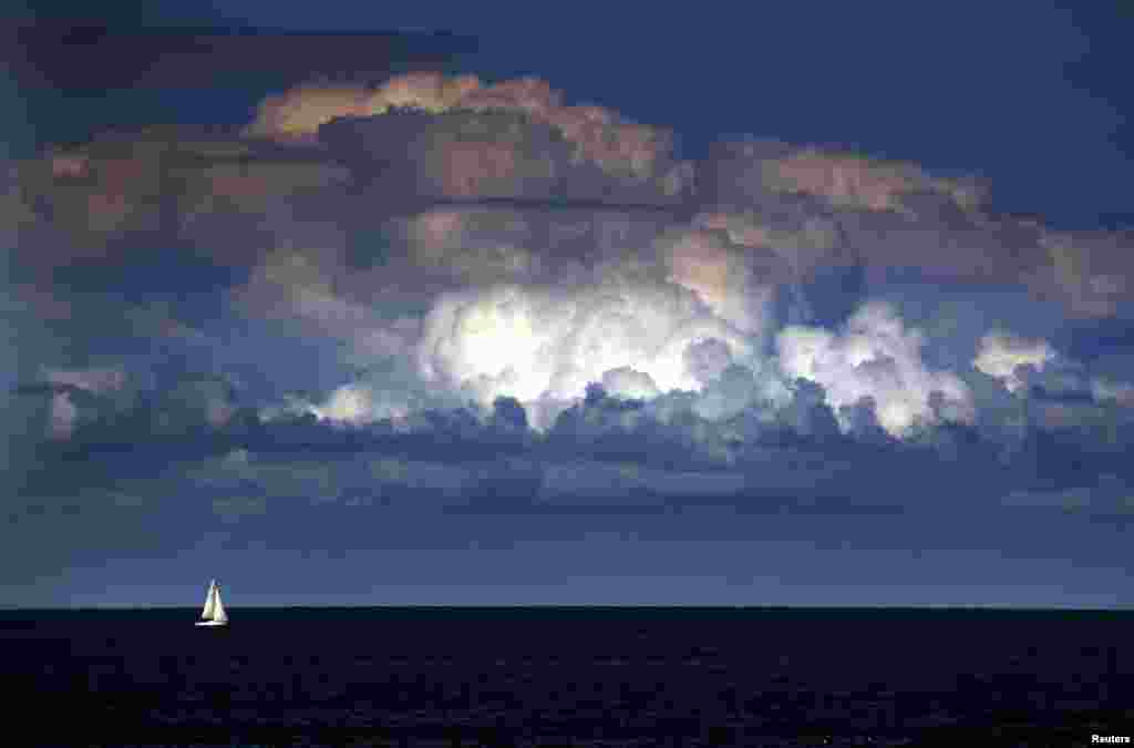 A storm cloud can be seen behind a yacht as it sails off the coast of Sydney, Australia, Mar. 31, 2014. The Bureau of Meteorology last week forecast 'warmer and drier than usual' weather extending into winter for Sydney and most of south-eastern Australia over the next three months.