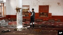 FILE - A man uses his mobile phone to take pictures inside a Shiite mosque hit by two bombs in Sana'a, Yemen, Sept. 3, 2015.