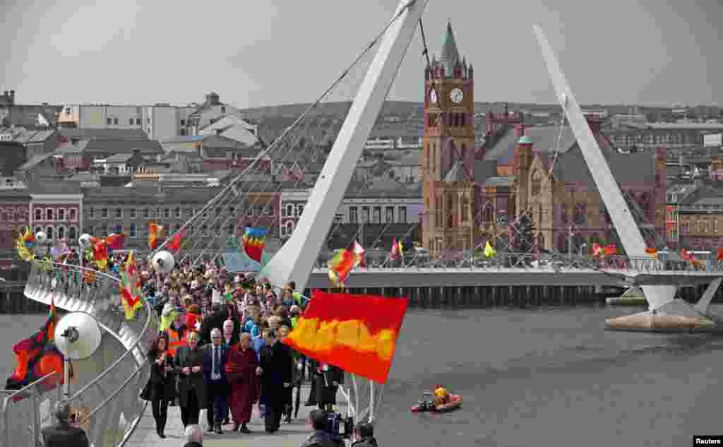 Tibetan spiritual leader the Dalai Lama walks across the Peace Bridge during his visit to Londonderry, northern Ireland.