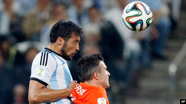 Argentina's Ezequiel Garay, left, and Netherlands' Robin van Persie go for a header during their World Cup semifinal soccer match at Itaquerao Stadium in Sao Paulo, July 9, 2014.