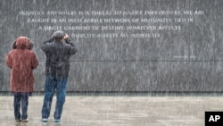 Dos turistas visitan el monumento a Martin Luther King, Jr. en Washington, en medio de una leve nevada.
