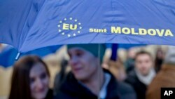 "Moldovan students hold an umbrella that uses the European Union symbol to form the sentence ""I am Moldova"" after arriving in the Romanian capital to vote, at the main railway station, Gara de Nord, in Bucharest, Romania, Sunday, Nov. 30, 2014. Moldovans"