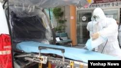 마포소방서 메르스 전담 119 구급대원이 18일 중동메르스 의심환자 이송 후 보호복과 마스크를 착용하고 구급차량을 소독하며 감염 관리에 온 힘을 쏟고 있다.