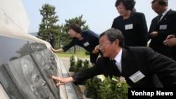 29일 제2 연평해전 전사자 유가족들이 기념비에 새겨진 전사자의 얼굴을 어루만지고 있다.