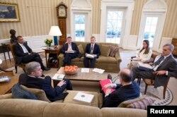 Suratdagi yagona ayol, Avril Heynz, Obama prezidentligi davrida Oq uydagi eng muhim rasmiylardan biri edi
