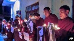 僧侶於1月25日在印度達蘭薩拉舉行的燭光晚會上,舉起他們聲稱藏人被當局槍殺的照片