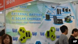An advertisement shows solar batteries that are compatible with Apple products, like the iPhone and iPad, at the Hong Kong Electronics Fair, October 13, 2011.