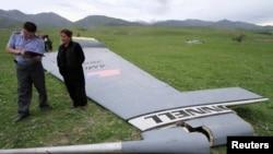 Seorang petugas tengah menanyai seorang penduduk yang berada di sekitar lokasi ditemukannya kepingan pesawat Boeing KC-135 Stratotanker, di desa Chaldovar, Kyrgyzstan (3/5). Pesawat militer AS tersebut jatuh hari Jumat (3/5), sekitar 160 kilometer dekat pangkalan udara AS, Bandara Internasional Manas, Kyrgyzstan .