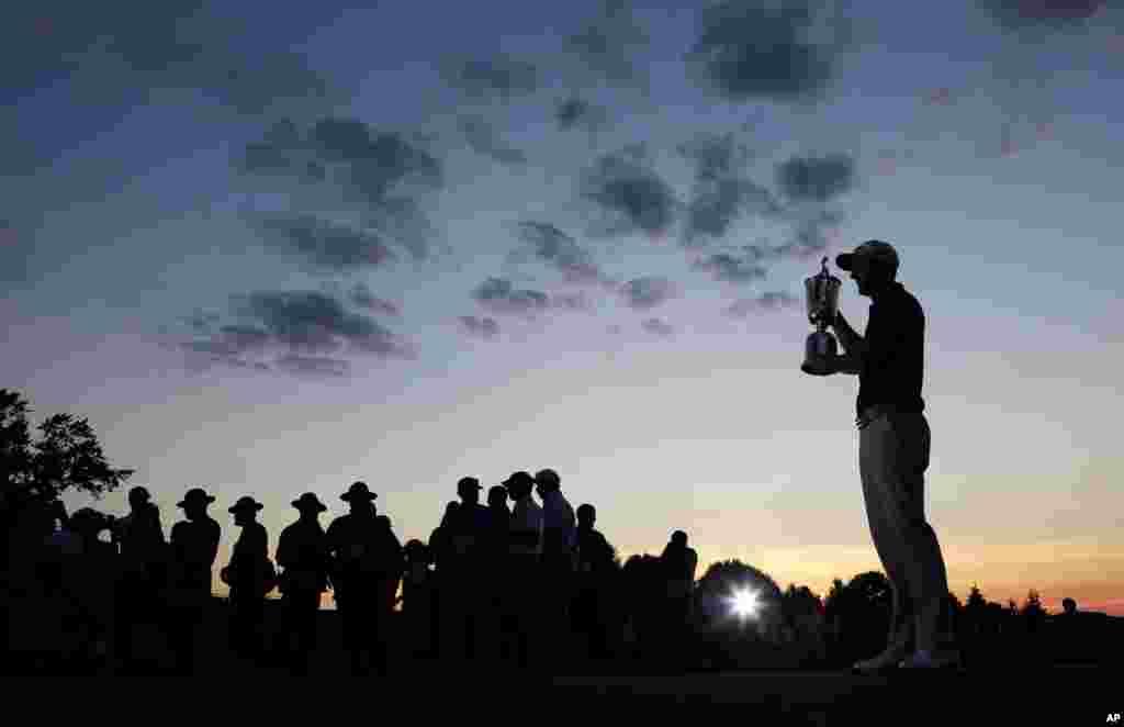 លោក Dustin Johnson កាន់ពានបន្ទាប់ពីបានឈ្នះពានរង្វាន់ជើងឯកវាយកូនហ្គោលដែលមានឈ្មោះថា U.S. Open នៅក្លឹប Oakmont Country Club ក្នុងក្រុង Oakmont រដ្ឋ Pennsylvania កាលពីថ្ងៃទី១៩ ខែមិថុនា ឆ្នាំ២០១៦។