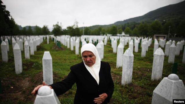 Mejra Dzogaz touches the graves of her two sons on May 17, 2012. Mejra's husband, three sons and a grandson were killed during the Srebrenica massacre in 1995 by a Serbian army unit commanded.
