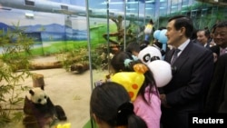 Taiwan President Ma Ying-jeou is accompanied by children as he looks at Tuan Tuan and Yuan Yuan inside their new enclosure at the Taipei City Zoo, January 24, 2009.