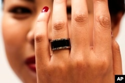 FILE - A woman shows a prototype of the Mota Smart Ring at the consumer electronic fair IFA in Berlin, Germany, Sept. 5, 2014. The smart ring is designed to notify users about incoming messages and phone calls, something, experts say, can be used to cheat on exams.