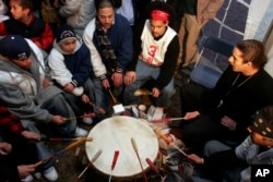 Members of the Mashpee Wampanoag tribe play a drum waiting for news that the tribe has won recognition as a sovereign American Indian nation, Feb 15, 2007, in Mashpee, Mass.