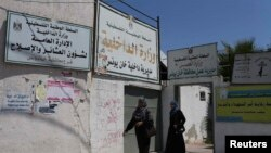 Palestinian Women walk past the closed office of the Ministry of Interior in Khan Younis in the southern Gaza Strip, June 26, 2014.