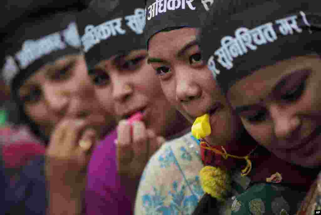 Nepalese women activists blow on a whistle as they participate in a protest demanding a provision in the new constitution to get citizenship in the name of one's mother in Kathmandu, Nepal.
