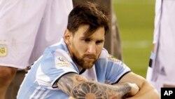 Déçu et assis sur la pelouse, Lionel Messi de l'Argentine attend la remise des médailles et du trophée après la défaite de la sélection argentine 2-4 face à celle du Chili lors de la Copa America Centenario, à East Rutherford, N.J., 26 juin 2016.