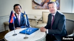 FILE PHOTO - Cambodian Deputy Prime Minister and Interior Minister Sar Kheng and Swedish Minister of the Interior Anders Ygeman smile after signing a cooperation agreement between the two countries in Stockholm, Sweden, May 25, 2015. (REUTERS)