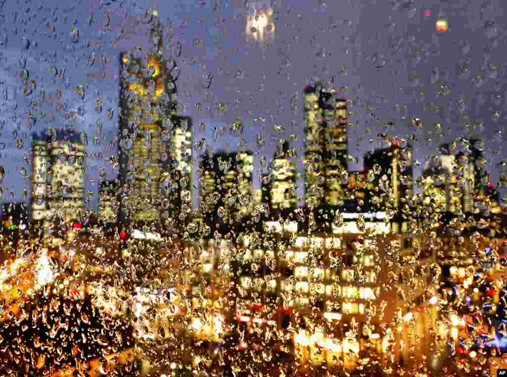 The buildings of the banking district are seen through thousands of rain drops on a glass railing in central Frankfurt, Germany.