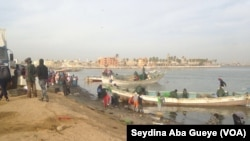 Des pêcheurs déchargent leurs pirogues à Guet Ndar, au Sénégal, le 4 février 2018.(VOA/Seydina Aba Gueye)