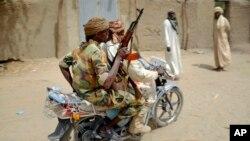 Des soldats tchdiennes patrouillent sur une moto dans le village de N'Gouboua, jeudi 5 mars 2015.