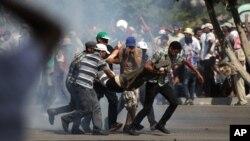 5일 무르시 대통령의 지지세력들이 카이로에서 경찰과 충돌한 가운데, 시위대가 부상자를 옮기고 있다.