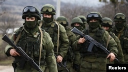 FILE - Armed men, Russian servicemen as the Kremlin later admitted, stand guard outside a Ukrainian military base in Perevalne, Crimea, March 9, 2014. Moscow's initial denials that the men were its soldiers was seen as part of its disinformation strategy.