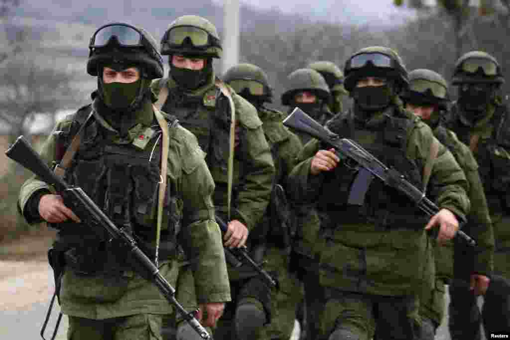 Armed men, believed to be Russian servicemen, march outside an Ukrainian military base in the village of Perevalnoye near the Crimean city of Simferopol, March 9, 2014.