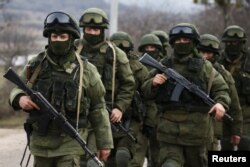 被认为是俄罗斯军人的武装分子行走在克里米亚的乌克兰军营外面
