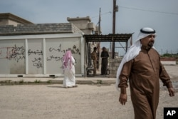 FILE - Residents visit the Kurdish Regional Government (KRG) headquarters in Rabia, northwestern Iraq, April 9, 2016. Critics say that for the KRG, everything is about internal Kurdish politics - even the fight against Islamic State is secondary to maintaining the upper hand politically.