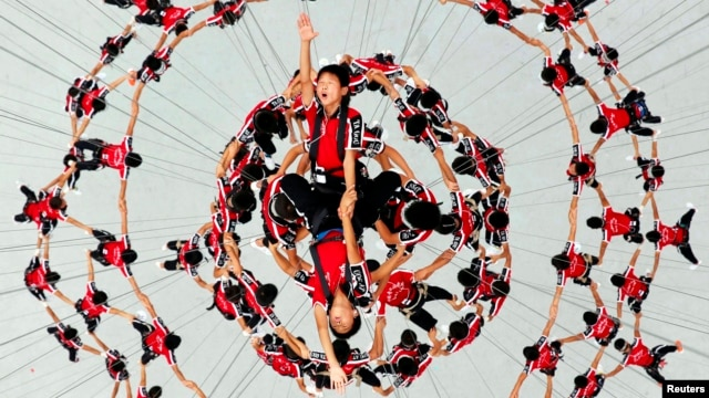 Students of Shaolin Tagou Martial Arts School are suspended in mid-air as they rehearse for the 2014 Youth Olympic Games' opening ceremony in Naning, China, Aug. 9, 2014.