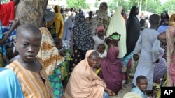 FILE - Civilians fleeing Islamist militants in the town of Bama take refuge at a school in Maiduguri. Nigeria's military says it has retaken Bama from Boko Haram.