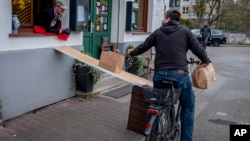 FILE - In this April 3, 2020, file photo, a man on a bike picks up food to go in front of the apple cider restaurant 'Zum Lahmen Esel' in Frankfurt, Germany. (AP Photo/Michael Probst, File)