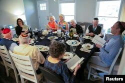 People laugh and joy as they read the Haggadah that haven't been able to do in person last year during a Passover Seder dinner party for 10 people vaccinated against the coronavirus disease, in Louisville, Kentucky, U.S. March 27, 2021. (REUTERS/Amira Karaoud)
