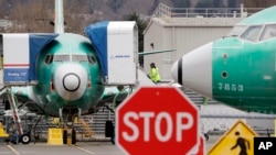 Boeing 737 MAX jets are parked Monday, Dec. 16, 2019, in Renton, Wash. Boeing will temporarily stop producing its grounded 737 MAX jet starting in January as it struggles to get approval from regulators to put the plane back in the air. (AP Photo/Elaine Thompson)