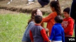 A volunteer plays with refugee kids in Idomeni on the Greek-Macedonian border. (J. Dettmer/VOA)