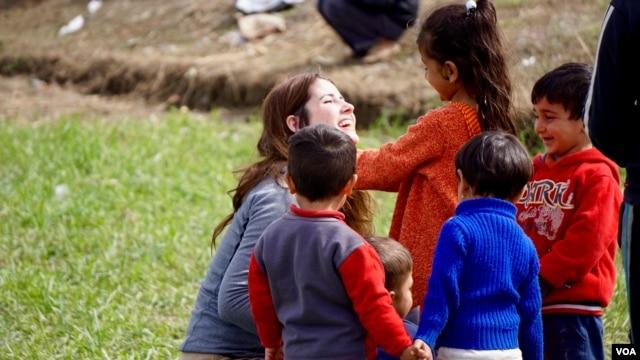 A volunteer plays with refugee kids in Idomeni on the Greek-Macedonian border. (J. Dettmer/VOA)