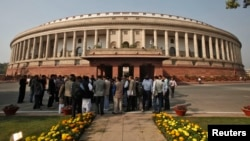 FILE - People stand in front of the Indian parliament building on the opening day of the winter session in New Delhi, Nov. 22, 2012.