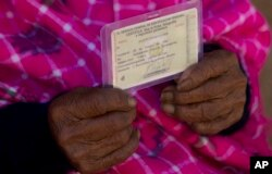 117-year-old Julia Flores Colque holds her identification card displaying her date of birth in Sacaba, Bolivia.