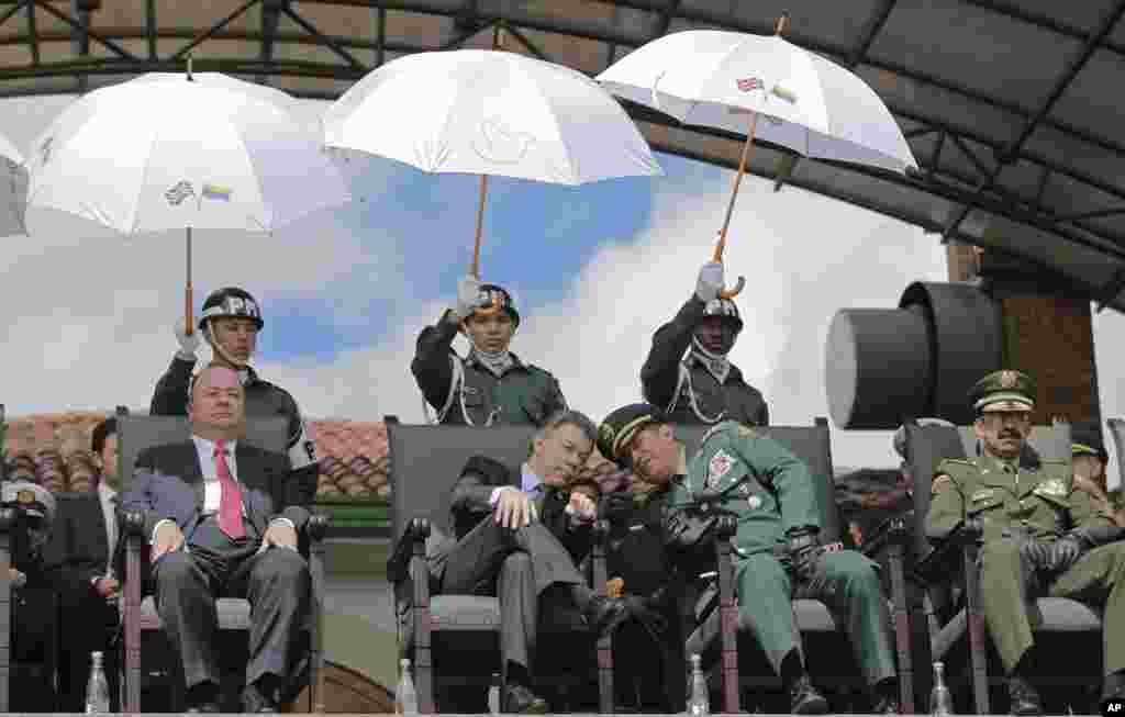 Colombia's President Juan Manuel Santos, center left, leans in to listen to Colombia's Armed Forces Commander Gen. Juan Pablo Rodriguez, during a military ceremony in Bogota, Colombia.