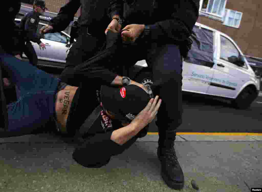 A protester is pushed by a Spanish riot police officer as an animal hospital van, said to be carrying the dog of the Spanish nurse who has Ebola, leaves from the nurse's home in Alcorcon, Spain. The dog, Excalibur, may be euthanized (put to sleep) to avoid possible spreading of Ebola. Animal rights activists are protesting to save the dog's life.