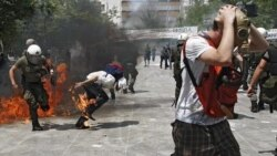 Riot police and demonstrators clash Tuesday during protests against austerity measures in Athens