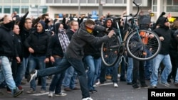 A man throws a bicycle during a demonstration by 'hooligans against Salafists and Islamic State extremist' in Cologne, Germany, Oct. 26, 2014.