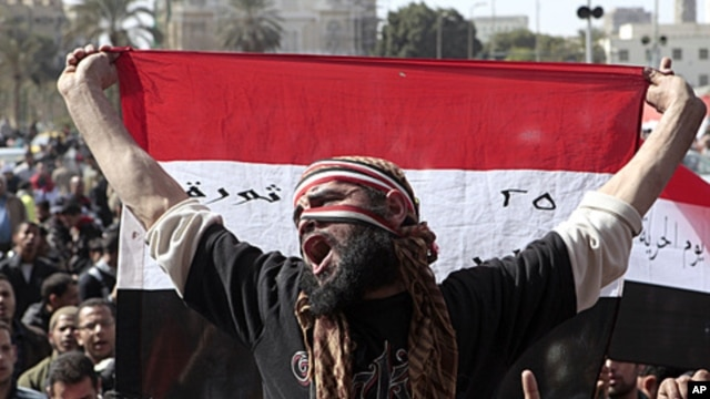 An Egyptian protester holds a national flag and chants anti-ruling military council slogans during a protest after Friday prayers at Tahrir Square, in Cairo, February 10, 2012.