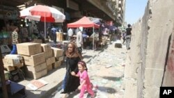 A child cries as she runs with her mother following a nearby double suicide bombing in Baghdad, 5 Sept 2010
