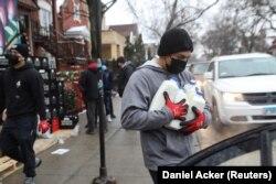 Miguel Angel Leonardo membawa susu ke kendaraan saat makanan didistribusikan di Chicago, Illinois, AS, 16 Maret 2021. (Foto: REUTERS/Daniel Acker)