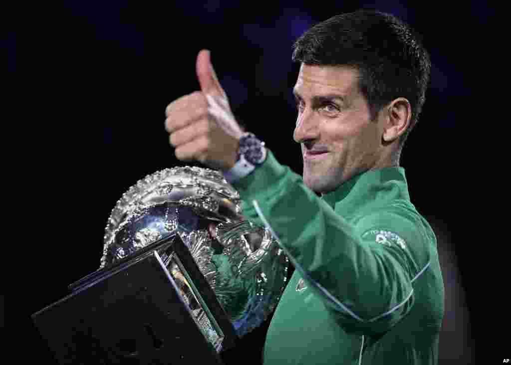 កីឡាករ Novak Djokovic នៃប្រទេសស៊ែប៊ីលើកមេដៃនៅពេលលោកកាន់ពានរង្វាន់ Norman Brookes Challenge Cup បន្ទាប់ពីបានឈ្នះកីឡាករ Dominic Thiem នៃប្រទេសអូទ្រីស នៅក្នុងការប្រកួតវគ្គផ្តាច់ព្រ័ត្រនៃការប្រកួត Australian Open Tennis Championship នៅក្នុងក្រុង Melbourne ប្រទេសអូស្ត្រាលី។