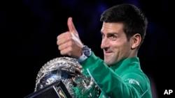 Petenis Serbia Novak Djokovic memberi isyarat ketika ia memegang setelah mengalahkan Austria Dominic Thiem di final kejuaraan tenis Australia Terbuka di Melbourne, Australia, Senin, 3 Februari 2020. (Foto: AP/Andy Brownbill)