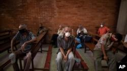 Personas, usando tapabocas como medida de precaución contra la propagación del coronavirus, esperan recibir una comida gratis en una iglesia en el barrio El Cementerio de Caracas, Venezuela. Mayo 22, 2020.